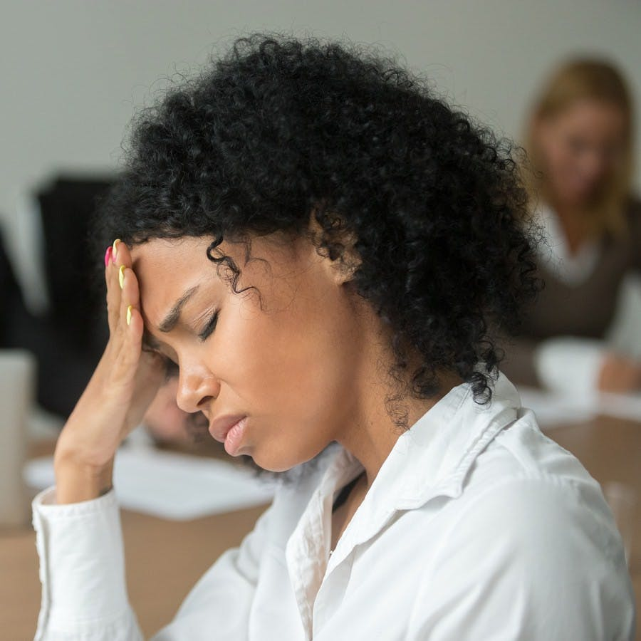 African american businesswoman feeling unwell from migraine pain touching forehead at team meeting