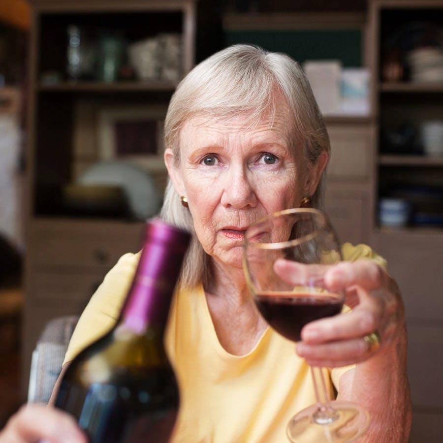 Older adult female offering a bottle of wine and glass sitting alone