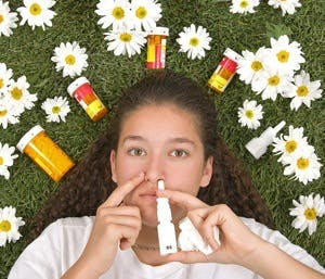 Girl on grass with medicines for allergies