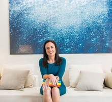 Amy Morin, LCSW, on a sofa in front of a painting discusses online therapy