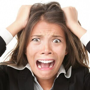 Stress. Woman stressed is going crazy pulling her hair in frustration. Close-up of young businesswoman on white.