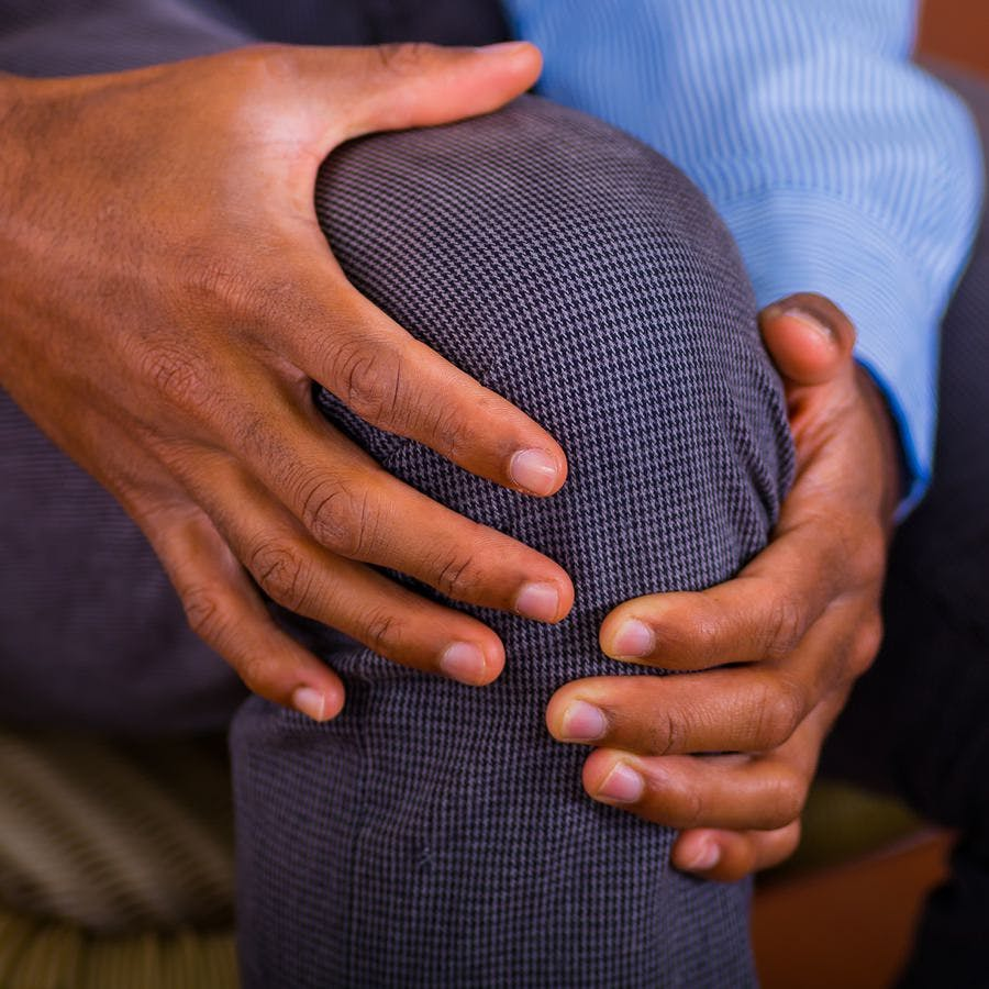 African american man holding his arthritic knee in pain