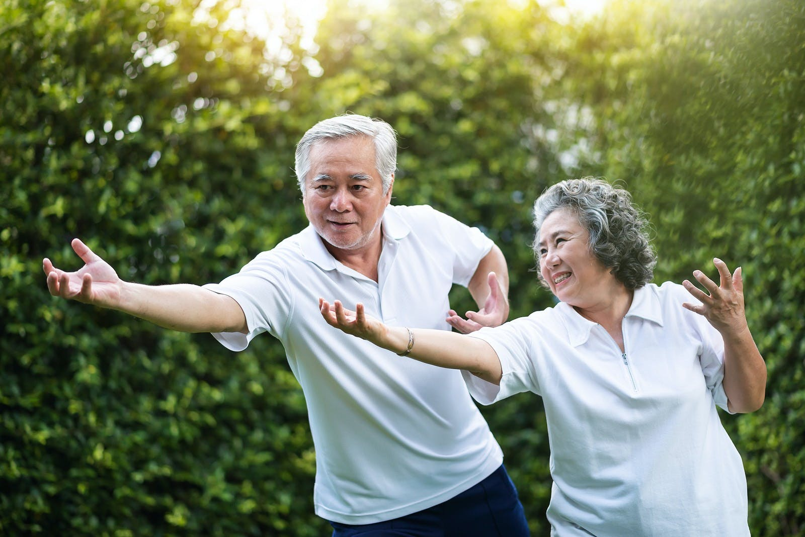 man and woman practicing tai chi outdoors