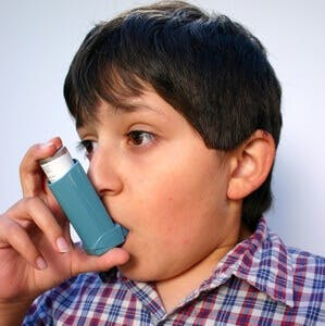 young boy with asthma using an inhaler