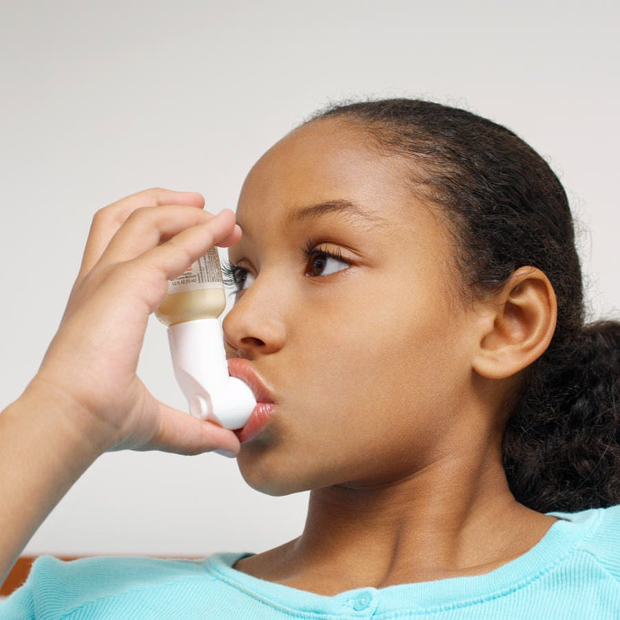 a young girl using an asthma inhaler, Primatene Mist