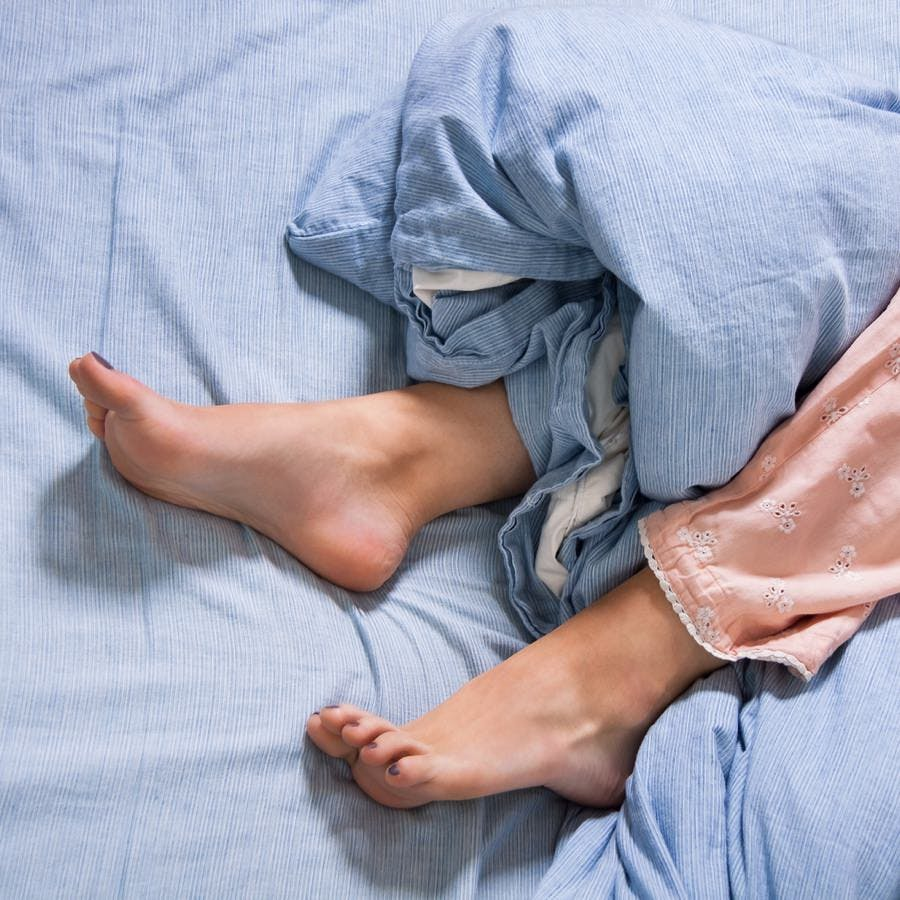 bare feet of a woman in bed with rumpled covers suffering from restless leg syndrome (needs RLS relief)