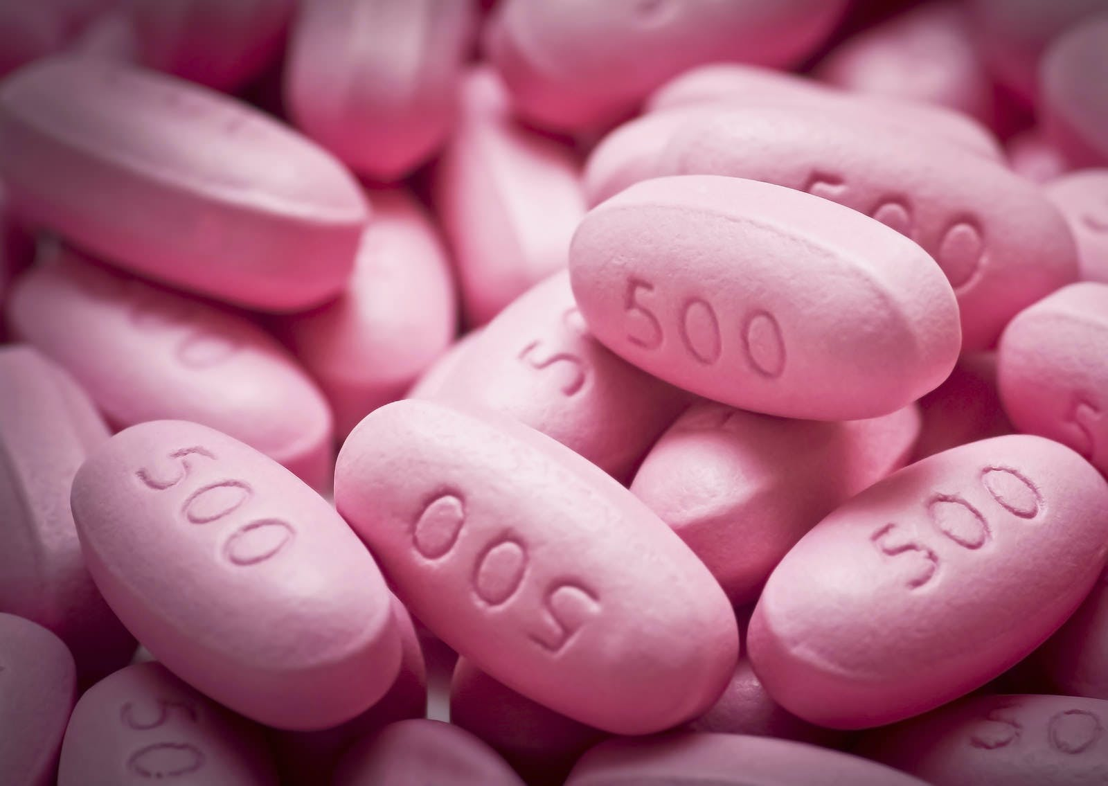 Close-up of many pink 500 milligrams pills.