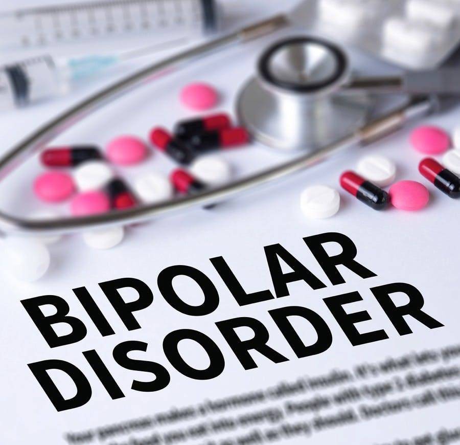 Sign reading Bipolar Disorder and an assortment of pills