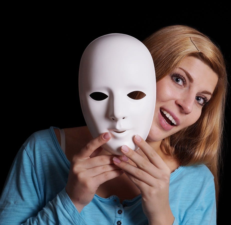 Young woman removing plain white mask from her face