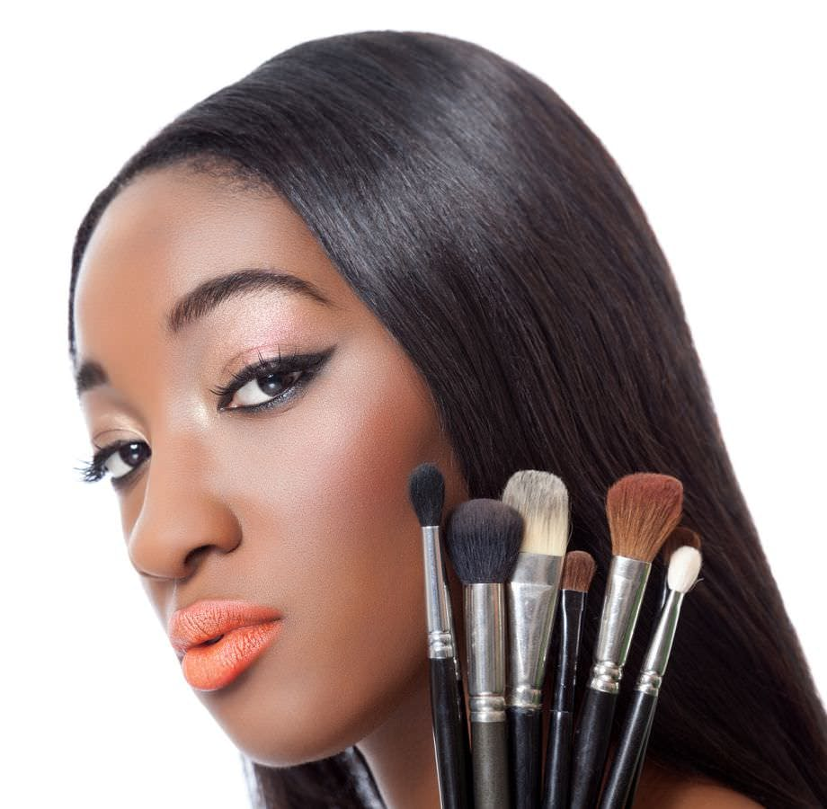 Black woman with straight hair holding makeup brushes isolated on white