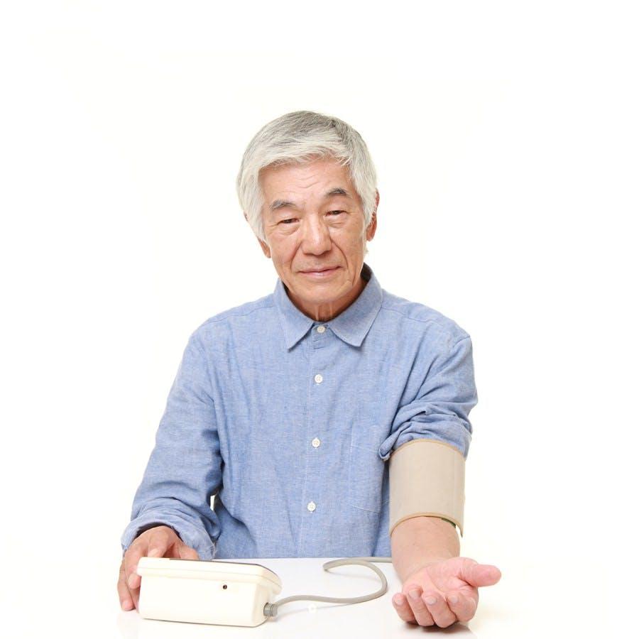Portrait of senior Japanese man checking his blood pressure on white background