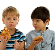 two young boys eating pizza