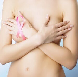 woman covering her bare breasts and has pink breast cancer ribbon