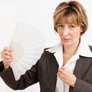 Businesswoman in Menopause fanning herself