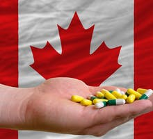 man holding pills in front of a Canadian Flag
