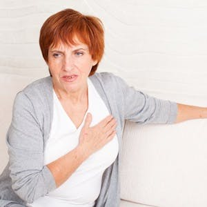 Cardiac pain. Mature woman holds her heart