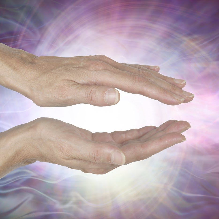 Channeling Vortex healing energy  – female hands held parallel with a white vortex energy formation and pink blue ethereal energy field  background