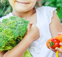 young girl holds colorful veggies