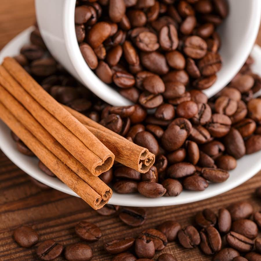 Coffee beans and cinnamon on a background of burlap. Roasted coffee beans background close up. Coffee beans pile from top with copy space for text. Seasoning. Spice. Cinnamon. Badian. Coffee house.
