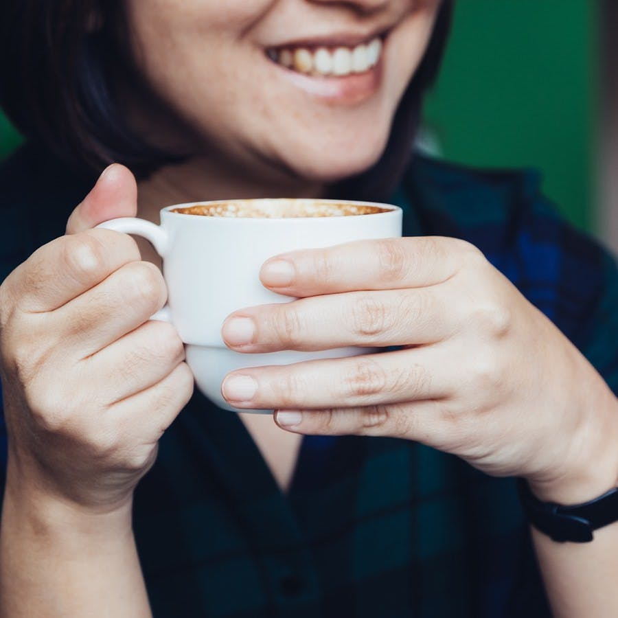 Close up woman hand holding hot cappuccino coffee cup with smiling face in cafe shop,leisure activity