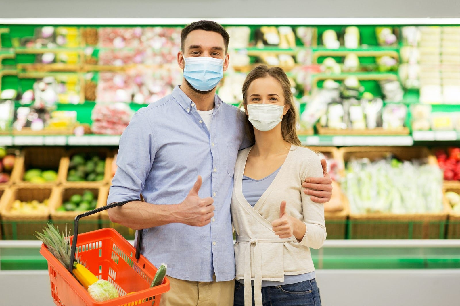 Shopping, sale, consumerism and people concept – happy couple wearing face protective medical masks for protection from virus disease with food basket at grocery store or supermarket showing thumbs up