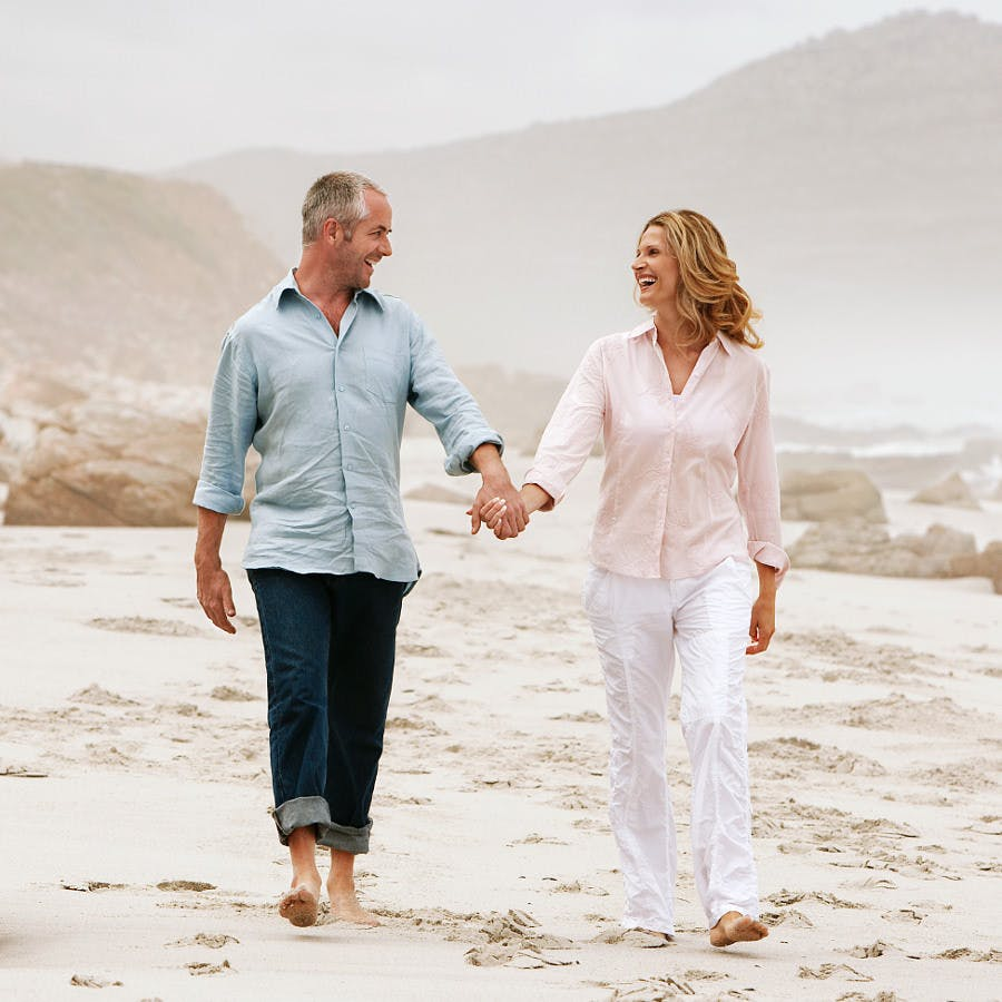 Loving Couple Strolling Hand in Hand on Beach