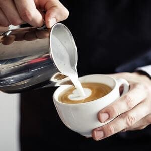 Closeup of barista making coffee and pouring milk