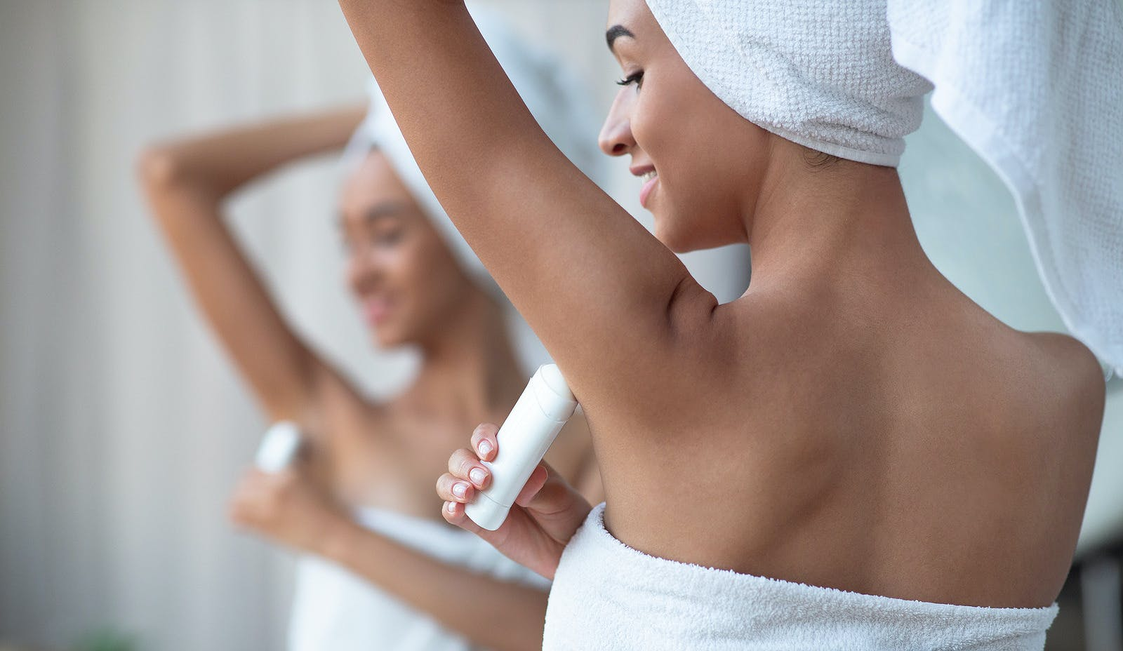 Deodorant for dry skin and purity concept. Smiling african american woman in white towel applying deodorant on armpit after shower stands in bathroom in reflection of mirror, panorama, free space