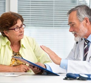 a male doctor talking to a female patient