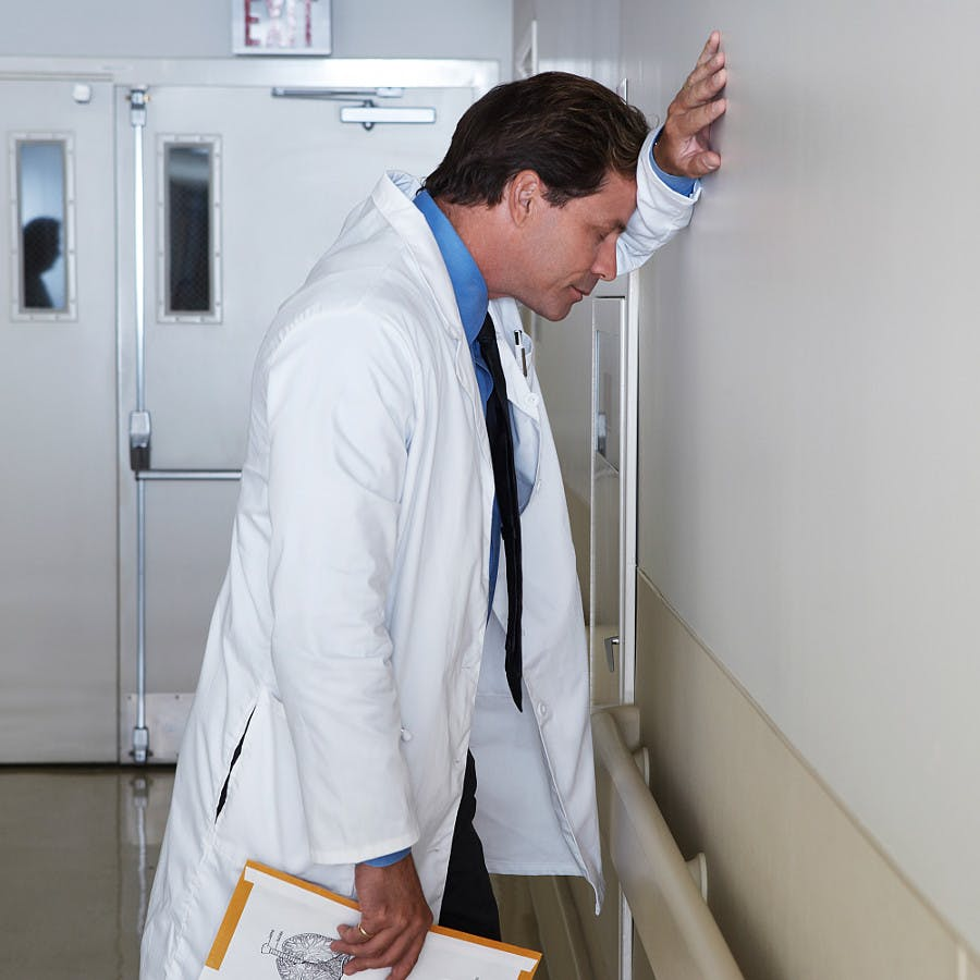 Depressed doctor leaning against wall in hospital corridor