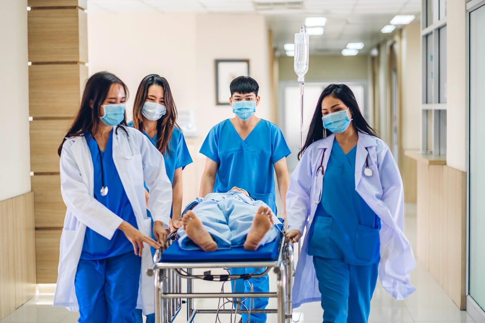 Group of professional medical doctor team and assistant with stethoscope in uniform taking seriously injured patient to operation emergency theatre room in hospital.health medical care concept