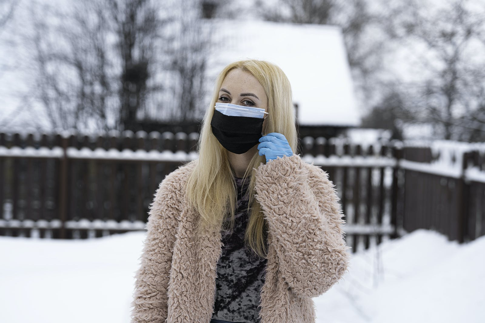 Double mask on the face. A girl in half a turn, with two masks on her face and a blue medical glove on her left hand, in the winter on the street