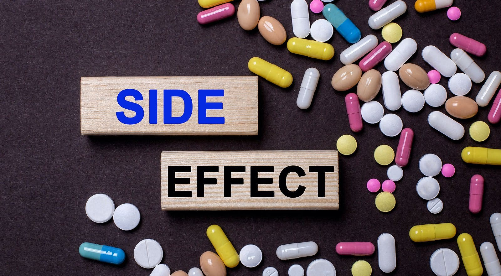 Side effect – words on wooden printed blocks between multi-colored tablets on a dark background