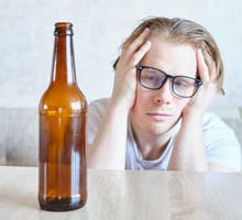 Man eyes empty brown bottle, wishing for hangover remedy that works