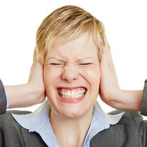 Woman with ear pain or a headache holding her head