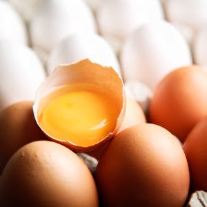 close up of eggs and one egg broken to show the egg yolk