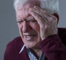 Elderly upset man with terrible cluster headache