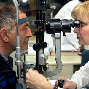 and ophthalmologist examines an older patient's eyes for macular degeneration and glaucoma