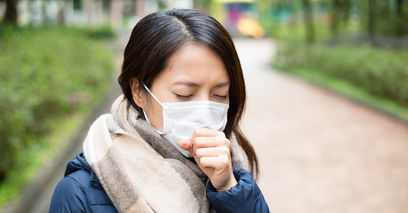 Woman wearing surgical facemask to protect from new virus and coughing into her hand