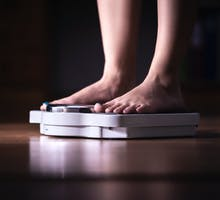 Woman weighing herself on a scale to determine weight gain