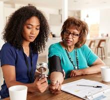 nurse using sphygmomanometer in home blood pressure measurement to determine if patient needs blood pressure medication to reduce blood pressure