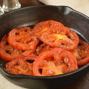 Closeup of fried tomatoes in a cast iron skillet