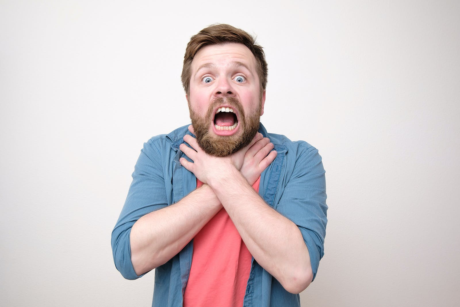 Frightened bearded man clutches his throat because of angioedema