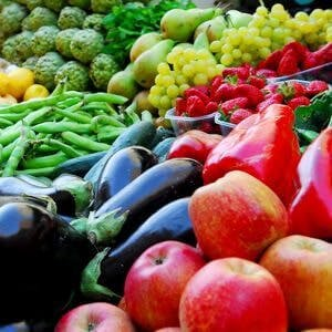 market display of apples, eggplants, peppers, grapes, green beans, colorful vegetables