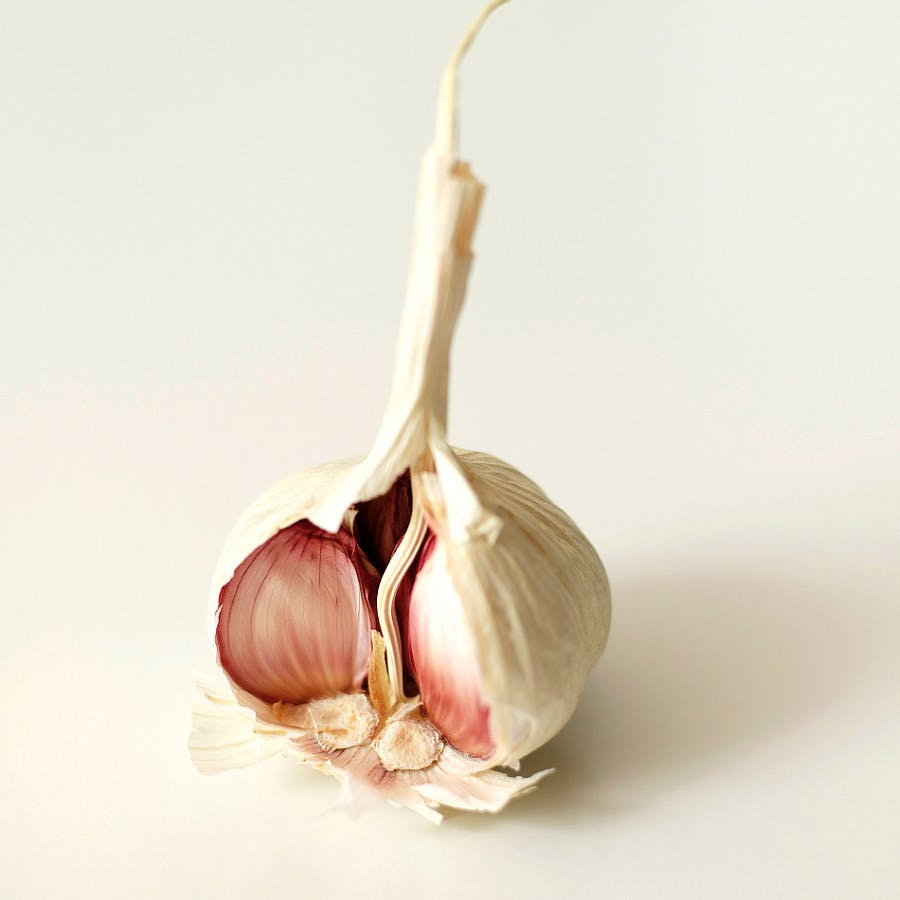 a garlic bulb split open to show the cloves