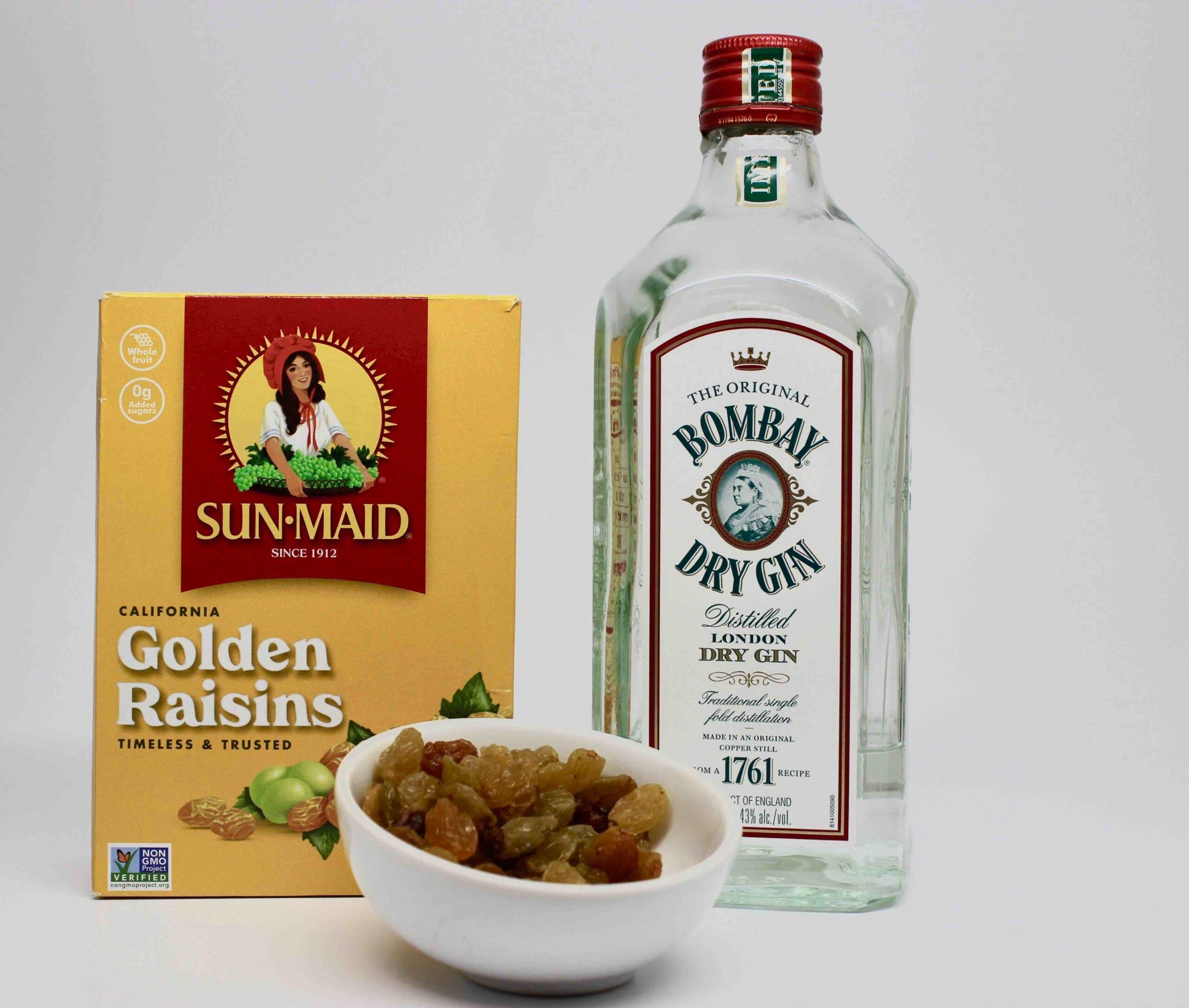 Box of golden raisins next to bottle of gin