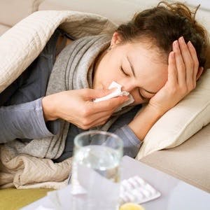 girl with cold or flu blowing her nose into a tissue
