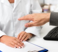patient demonstrating hand tremor to physician