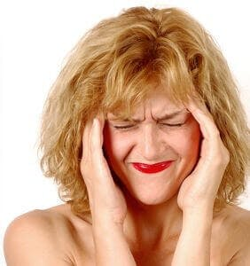 woman with a migraine headache massages her temples