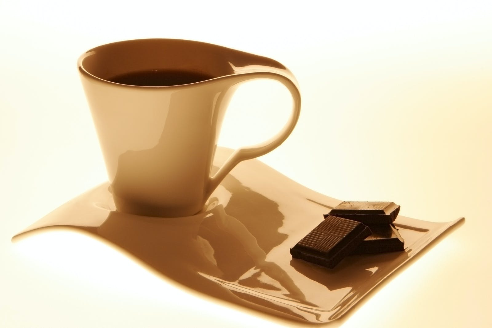 Coffee glass and the chocolate on a white background